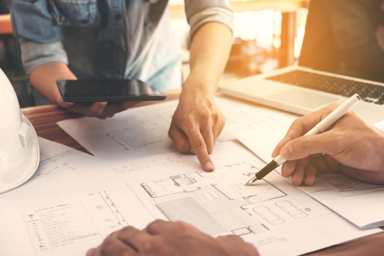 Architects working on blueprint on office