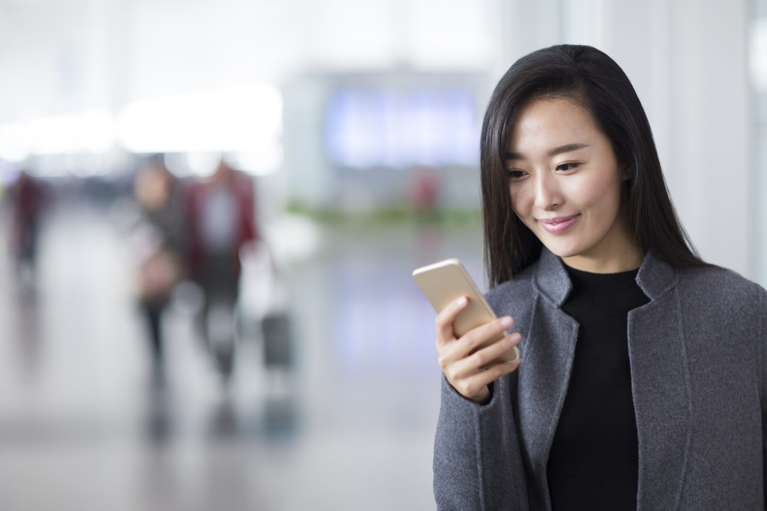 Businesswoman using smart phone in airport