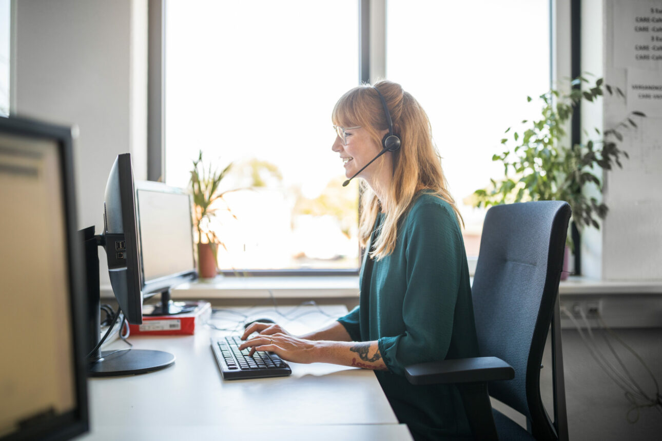 Side view of customer service representative using computer